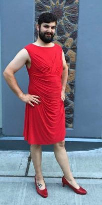 A bearded person in a sleeveless red dress