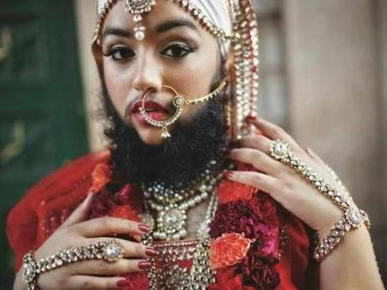 A bearded person wearing feminine jewelry and a nose ring with orange flowers on their V cut clothing.